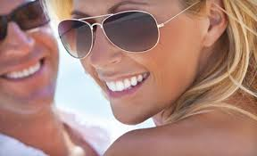 Woman in sunglasses with white teeth
